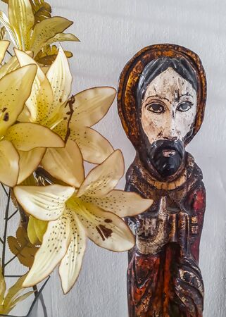 Wooden jesuschrist sculpture at table at interior room house