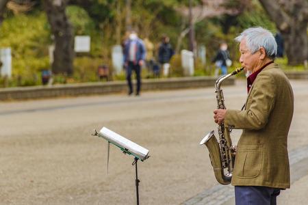 TOKYO, JAPAN, JANUARY - 2019 - Senior japanese man playing the saxophone at ueno park, tokyo city, japan 에디토리얼