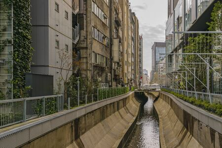 Small stream surrounded by apartment buildings at shibuya district in tokyo city, japan