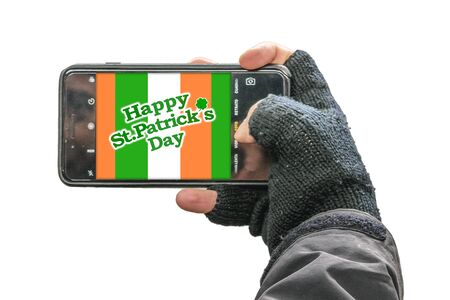 Person hand holding mobile phone with saint patricks design on the screen