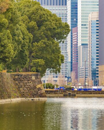 Imperial garden lake and walls and modern buildings at background in chiyoda district in tokyo city, japan