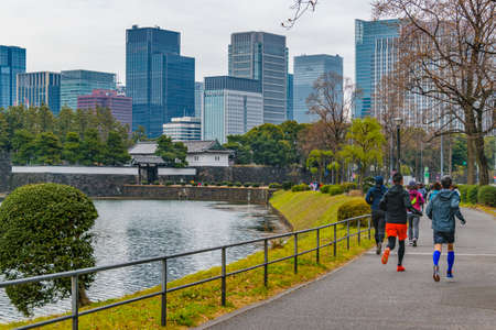 TOKYO, JAPAN, JANUARY - 2019 - People running at exterior imperial palace park in chiyoda district, tokyo, japan
