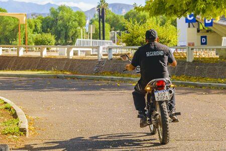 MENDOZA, ARGENTINA, APRIL - 2019 - Back view security worker driving motorcycle, mendoza capital, argentina
