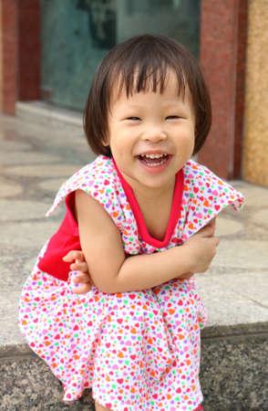 vietnamese ethnicity: smile asian girl sitting on the ground Stock Photo