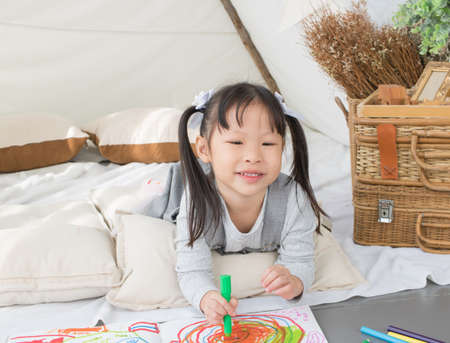 Asian little girl painting on paper in white room at home