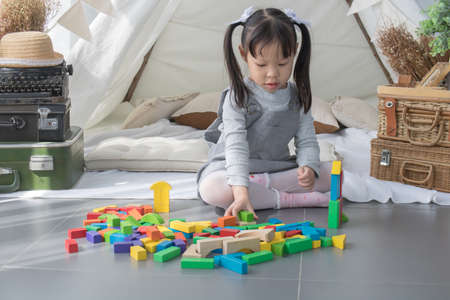 Asian little girl playing colourful blocks in white room