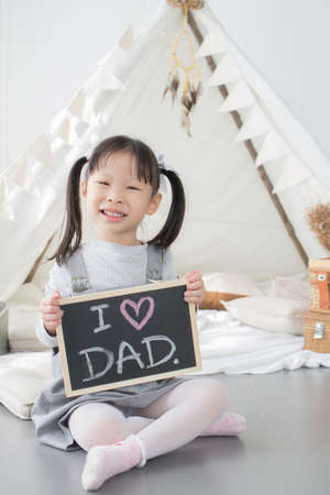 Asian little girl sitting and holding  I LOVE DAD board in white room at home