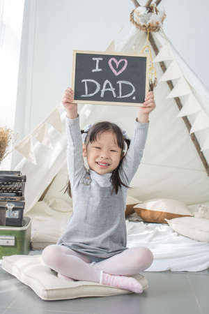 Asian little girl holding  I LOVE DAD board above her head in white room at home