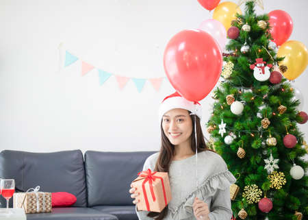 Asian beautiful woman holding gift box. Smiling face in room with decorated Christmas tree Standard-Bild