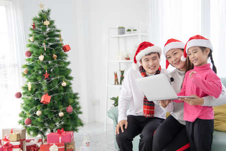 Happy Asian family using a laptop for shopping online in Christmas Day