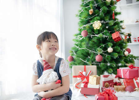Cute Asian little girl holding Santa Claus doll in room with decorated with Christmas tree