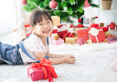 Cute Asian little girl lying in room with decorated with Christmas tree Standard-Bild