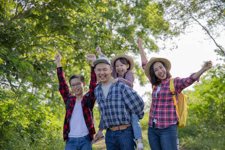 Happy asian family trekking together on vacation