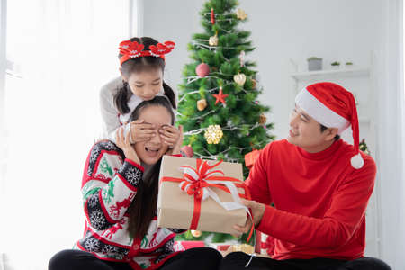 Daughter surprising her mother with a Christmas gift while her father holding a gift. Standard-Bild