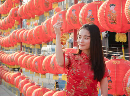 Asian pretty girl in Chinese dress holding Chinese new year ornament