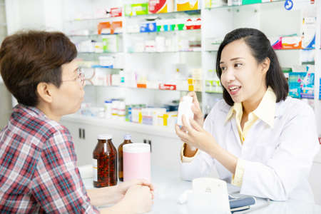 Beautiful asian pharmacist advice about medicine to female customer in drugstore