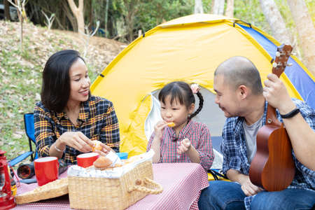 Happy asian family camping in forest, eating orange fruit together Standard-Bild