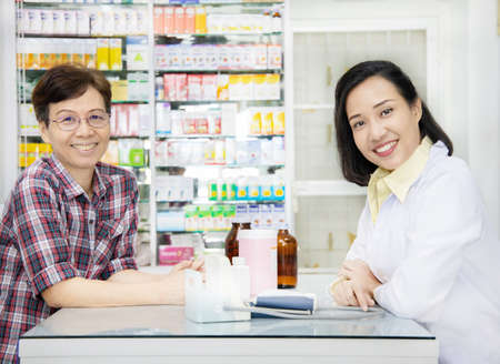 Asian pharmacist advice about medicine to female customer in drugstore