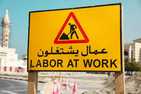 Road sign writen on a arab and english language in United Arab Emirates  Building construction of mosque in background  photo