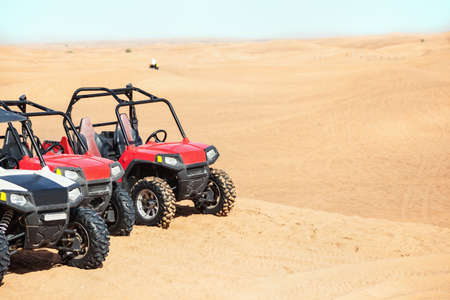 quad: Several buggies in the desert.