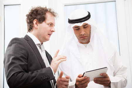 Two businessmen people working and discussing using digital tablet photo
