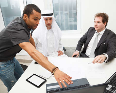 african descent: Young architect showing his project to business partners Stock Photo