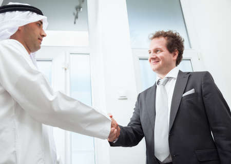 arab: Businessmen congratulating each others business success.  Stock Photo