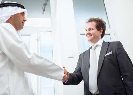 personas saludandose: Los hombres de negocios felicitando el éxito del negocio de cada uno.