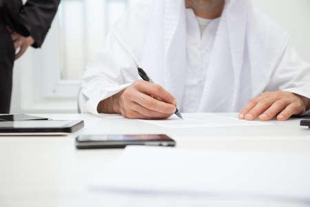 hombre arabe: Cierre de negocios �rabe de firmar el contrato. El foco est� en la mano Foto de archivo