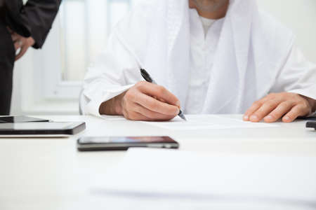 filling out: Close up of Arab businessman signing the contract. Focus is on hand