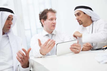homme arabe: Un groupe de gens d'affaires travaillant et en discutant. L'accent est mis sur la tablette