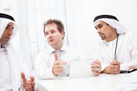 hombre arabe: Grupo de gente de negocios trabajando y discutiendo. El foco est� en la tableta