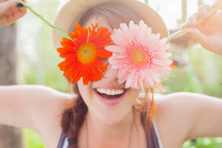 spring time: Young woman covering her eyes with fresh colorful flowers. Enjoying spring time Stock Photo