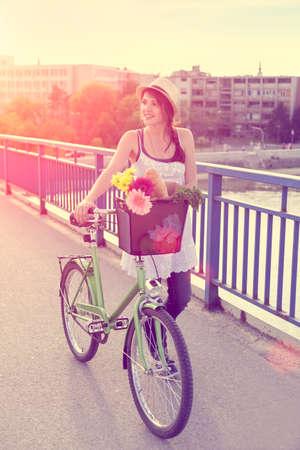 바구니에 꽃이 그녀의 자전거와 함께 다리를 건너 아름 다운 젊은 여자.