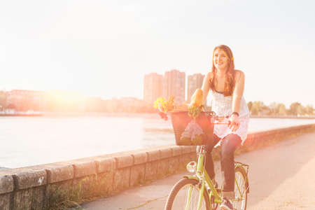 Beautiful young woman riding bicycle with flowers in basket and enjoying summer time. photo