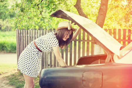 Beautiful retro style woman searches the trunk of old timer car. photo