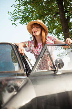 oldtimer: Portrait of beautiful retro style woman standing next to old timer car