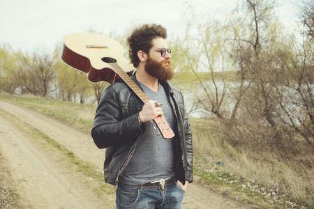 man playing guitar: Bearded man playing guitar