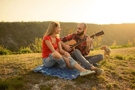 자연 속에서 연인입니다. 젊은 부부 기타에 일몰 시간에 기타를 연주하는 동안 공원에 앉아 사랑에. 개와 함께 스톡 콘텐츠