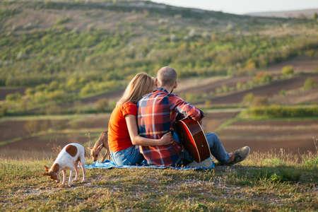 젊은 부부 기타에 일몰 시간에 기타를 연주하는 동안 공원에 앉아 사랑에. 개와 함께 스톡 콘텐츠