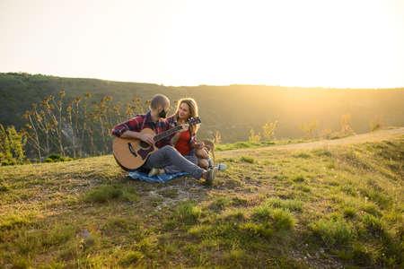 젊은 부부 기타에 일몰 시간에 기타를 연주하는 동안 공원에 앉아 사랑에.