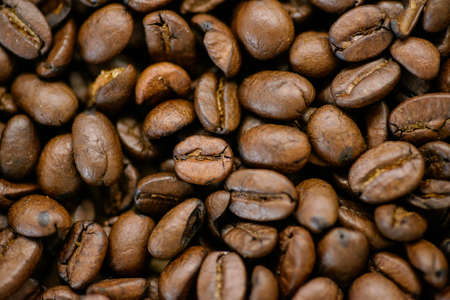 Roasted coffee beans on rustic wooden table background