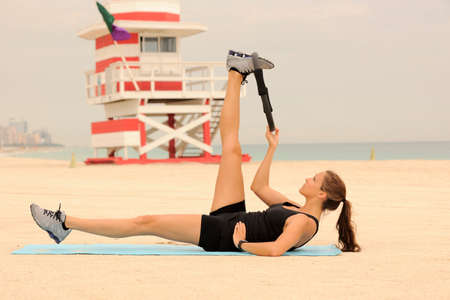 Beautiful fitness model demonstrating leg stretch with Pilates ring on Miami Beach. Imagens - 34430604