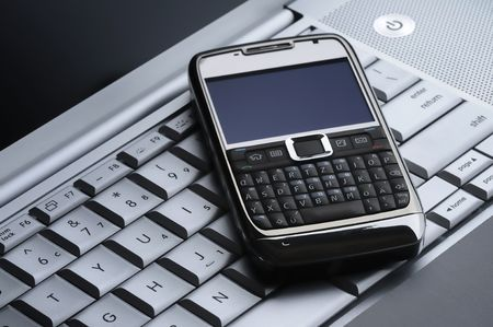 smart cell phone on a silver laptop Stock Photo - 5205155