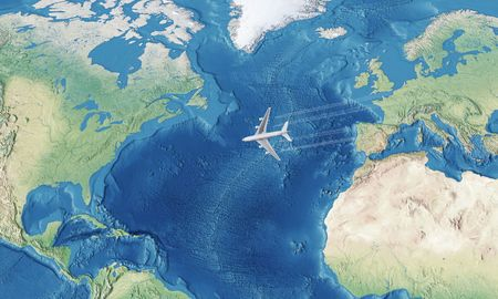 White Civil Airplane over the Atlantic ocean flying from Europe to the USA