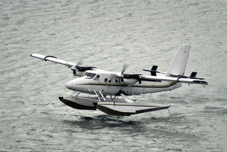 twin propeller engine hydroplan taking off from water surface photo