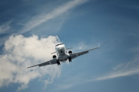 passenger private jet landing on a clear blue sky