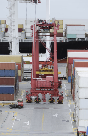 Cargo containers truck and a crane in storage area of freight port terminal