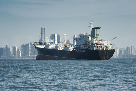 panama city beach: View of a large cargo ship anchored and the city skyline at the background, Panama Stock Photo