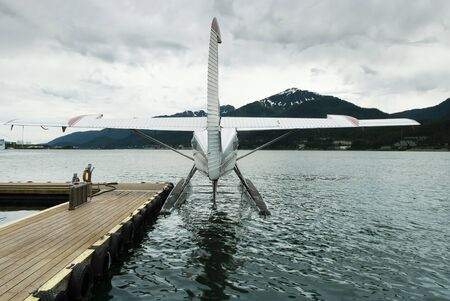 dock: Seaplane docked at the port of Juneau with storm clouds overhead, Alaska Stock Photo